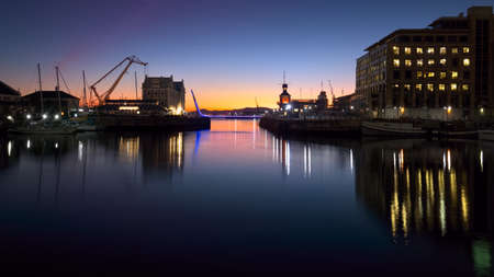 Evening view of a harbor entrance and its pedestrian swing bridge edged with neon strip lights. Stock Photo