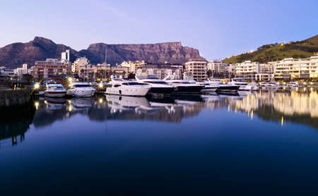 Table Mountain is reflected in the still waters of a marina for luxury motor yachts in Cape Town, South Africa. Stock Photo