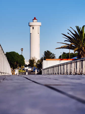Milnerton Lighthouse as viewed from the new wooden bridge across the Diep River. Woodbridge Island, Cape Town, South Africa. Stock Photo