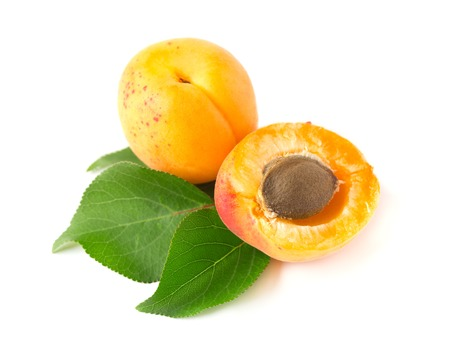 apricot kernels: Ripe apricot with a stone and leaves, isolated on white background Stock Photo