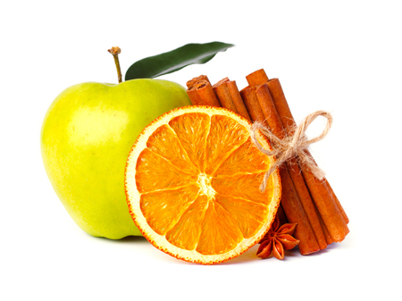 Fresh apple, a slice of dry orange and aromatic cinnamon sticks, star anise isolated on white background.