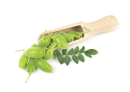 pea pod: Green chickpeas in the pod on a wooden spoon isolated on white background