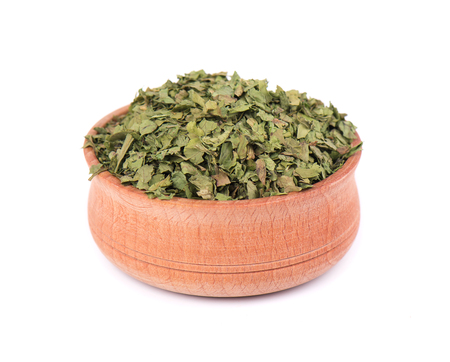 Dried cilantro in wooden bowl for spices isolated on white background. Crushed cilantro. Dried parsley leaf. Closeup.