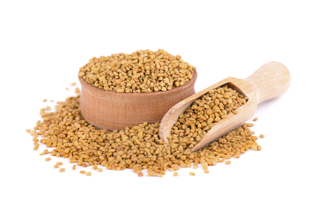 Fenugreek seeds in wooden spoon, isolated on white background. Zdjęcie Seryjne