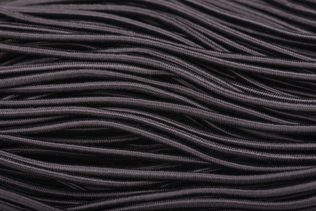 Black elastic band for sewing clothes. Sewing rubber band. Elastic for clothing texture background. Фото со стока