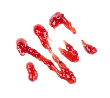 Confettura di fragole spessa pioggerella, isolato su sfondo bianco. Marmellata di fragole, salsa, gocce di topping. Vista dall'alto.