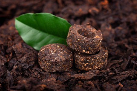 Aromatic black pu-erh tea. Fermented and compressed Leaves into bricks. Round flat disc of puer tea. Healthy drink.
