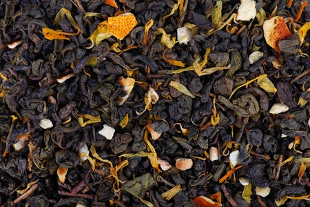 Green Ceylon tea with dry flowers and candied orange background. Фото со стока