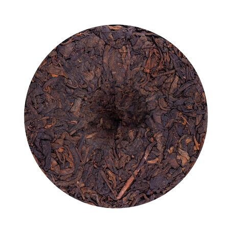 Round flat disc of puer tea isolated on white background. Chinese tea Shou Puer. Pressed fermented Pu-erh tea. Macro close up. Aromatic black puer tea. Healthy drink 版權商用圖片