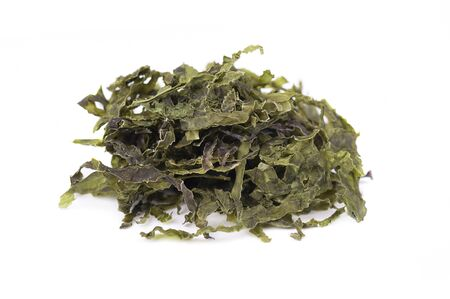 Dry wakame seaweed, isolated on white background. Sea kale, asian dry food