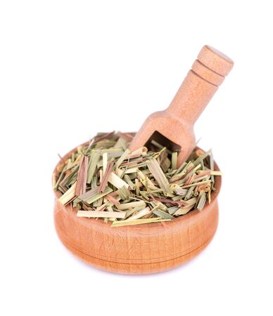 Lemongrass in a wooden bowl and spoon, isolated on a white background. Dry sprigs of natural lemongrass