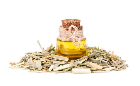 Lemongrass essential oil in a glass bottle, isolated on a white background. Dry sprigs of natural lemongrass Banque d'images