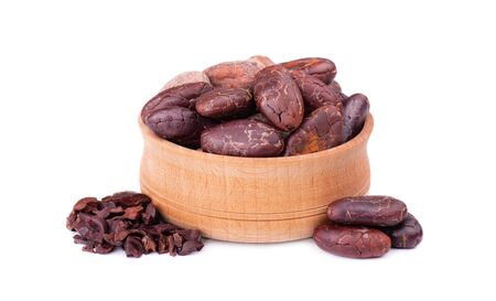 Peeled cocoa beans in the wooden bowl, isolated on white background. Roasted and aromatic cocoa beans, natural chocolate