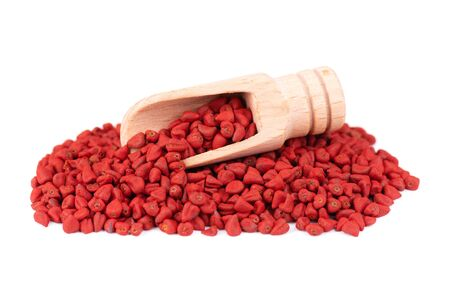 Annatto seeds, in the wooden spoon, isolated on white background. Achiote seeds, bixa orellana. Natural dye for cooking and food. Close-up