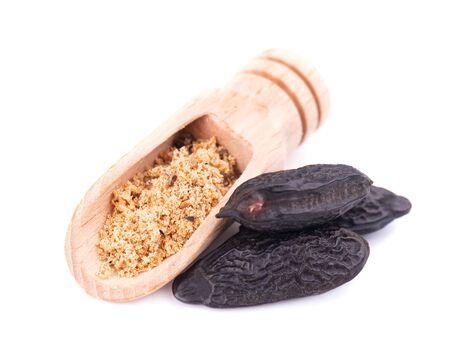 Tonka beans isolated in the wooden spoon, on white background. Bean of Dipteryx odorata, cumaru or kumaru. Fresh aroma tonka beans