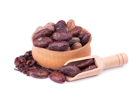 Peeled cocoa beans in the wooden bowl, isolated on white background. Roasted and aromatic cocoa beans in wooden spoon, natural chocolate Stok Fotoğraf