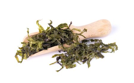 Dry wakame seaweed, isolated on white background. Sea kale, asian dry food in a wooden spoon