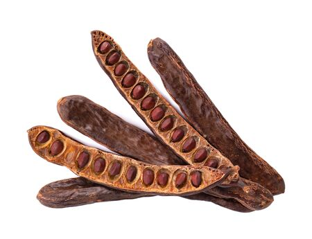 Ripe carob pods and bean isolated on white background. Top view