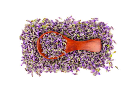 Lavender flowers on a wooden spoon, isolated on white background. Petals of lavender flowers. Medicinal herbs. Top view Archivio Fotografico