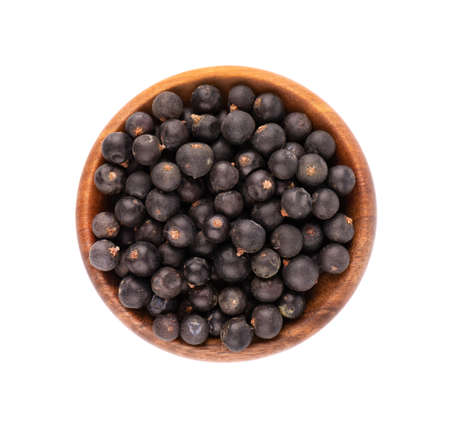 Dry juniper berries in wooden bowl, isolated on white background. Top view