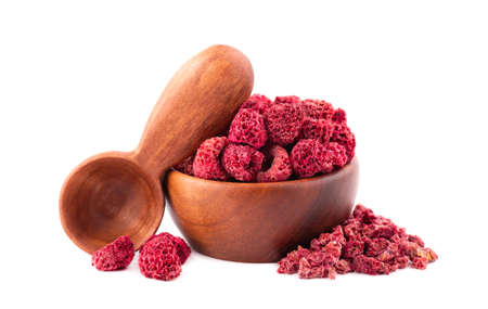 Dried raspberry isolated on white background. Dehydrated raspberry in wooden bowl and spoon 스톡 콘텐츠