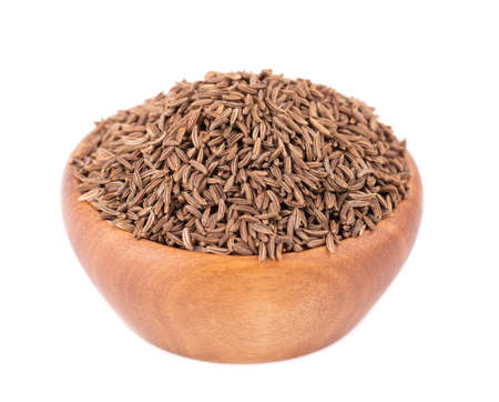 Cumin seeds in wooden bowl, isolated on white background. Cumin seeds or caraway Stock fotó