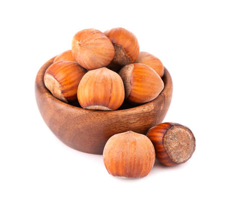 Hazelnut in wooden bowl, isolated on white background. Nut macro. With clipping path