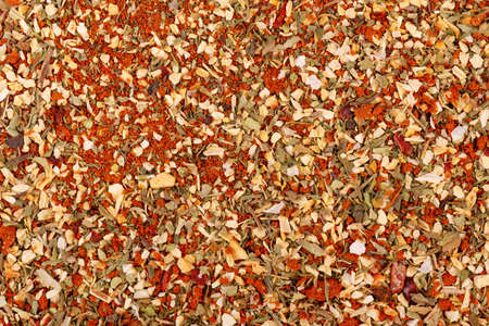 Mix of herbs, spices and dry tomatoes, background. Natural organic food seasoning