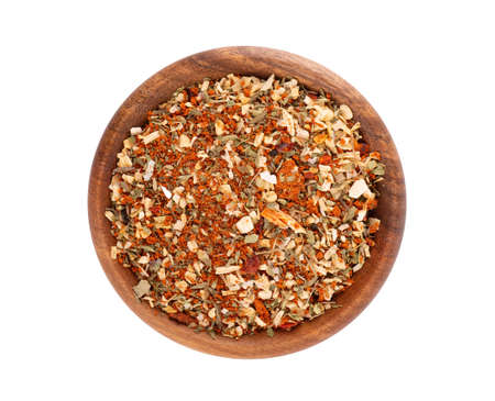 Mix of herbs, spices and dry tomatoes in wooden bowl, isolated on white background. Natural organic food seasoning. Top view