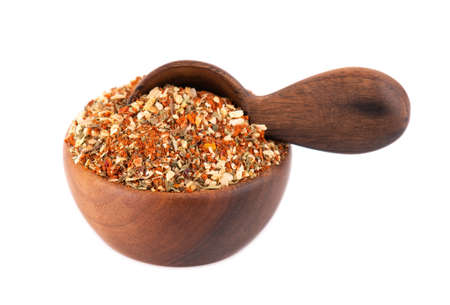 Mix of herbs, spices and dry tomatoes in wooden bowl and spoon, isolated on white background. Natural organic food seasoning