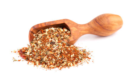 Mix of herbs, spices and dry tomatoes in wooden scoop, isolated on white background. Natural organic food seasoning