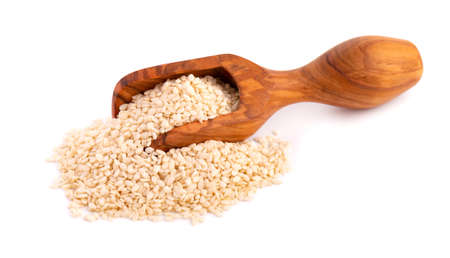 Sesame seeds in wooden scoop, isolated on white background. Organic dry sesame seeds