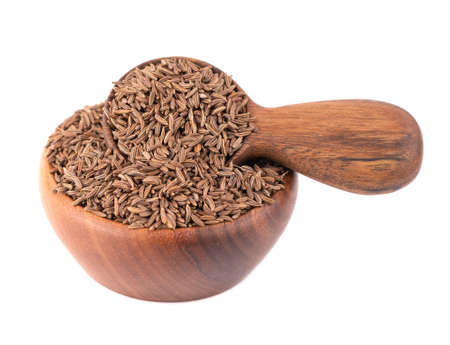 Cumin seeds in wooden bowl and spoon, isolated on white background. Cumin seeds or caraway 스톡 콘텐츠