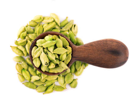 Cardamom seeds in wooden spoon, isolated on white background. Pile of green cardamom pods. Top view