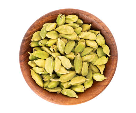 Cardamom seeds in wooden bowl, isolated on white background. Pile of green cardamom. Top view 스톡 콘텐츠