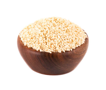 Sesame seeds in wooden bowl, isolated on white background. Organic dry sesame seeds