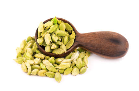 Cardamom seeds in wooden spoon, isolated on white background. Pile of green cardamom pods. 스톡 콘텐츠