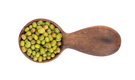 Mung beans in wooden spoon, isolated on white background. Vigna radiata. Top view.