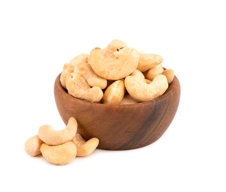 Cashew nuts in wooden bowl, isolated on white background. Roasted cashew nuts. Banco de Imagens