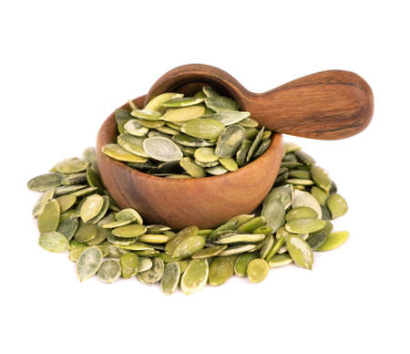 Pumpkin seeds in wooden bowl and spoon, isolated on white background. Green pepita seeds.