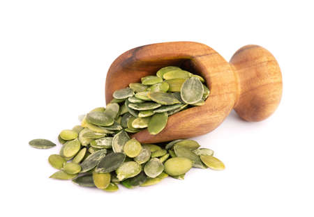 Pumpkin seeds in wooden scoop, isolated on white background. Green pepita seeds. Banco de Imagens