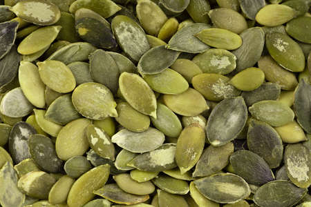 Pumpkin seeds background. Green pepita seeds. Top view. Banco de Imagens
