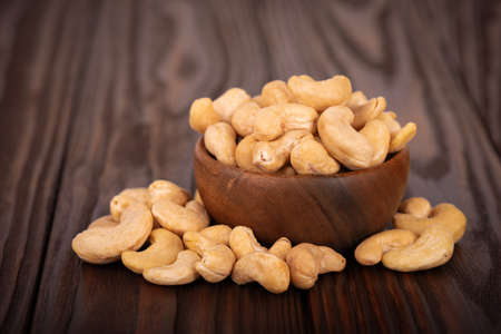 Cashew nutsin wooden bowl, on wooden background. Roasted cashew nuts. Banco de Imagens