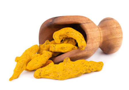 Dry turmeric root in wooden scoop, isolated on white background. Curcuma longa linn.
