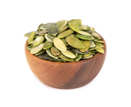 Pumpkin seeds in wooden bowl, isolated on white background. Green pepita seeds.
