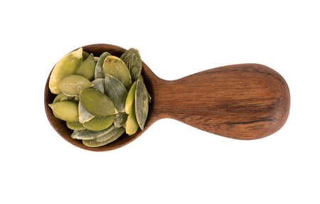 Pumpkin seeds in wooden spoon, isolated on white background. Green pepita seeds. Top view.