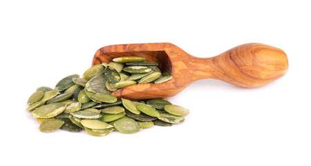 Pumpkin seeds in wooden scoop, isolated on white background. Green pepita seeds. 版權商用圖片
