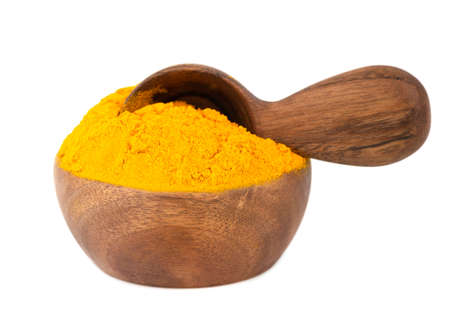 Dry turmeric powder in wooden bowl and spoon, isolated on white background. Curcuma longa linn.