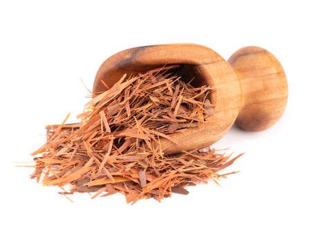 Lapacho herbal tea in wooden scoop, isolated on white background. Natural Taheeboo dry tea. Pau darco herb. Tabebuia heptophylla.