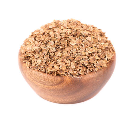 Dill seeds in wooden bowl, isolated on white background. Natural dry dill seeds. Anethum graveolens. 版權商用圖片
